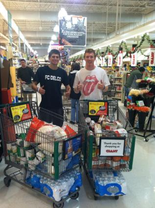 Athletes C.A.R.E. Members Ryan Dodds (Left) and Tom McCutcheon (Right) purchasing food for Thanksgiving CANS FOR C.A.R.E. Drive